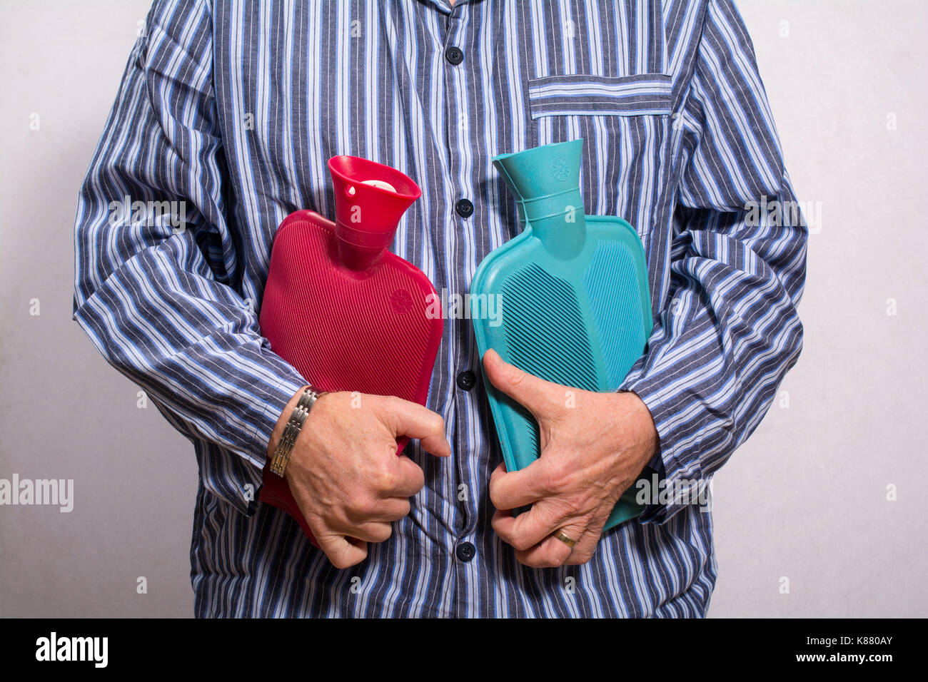 Man in striped pyjamas holding two hot water bottles - Stock Image