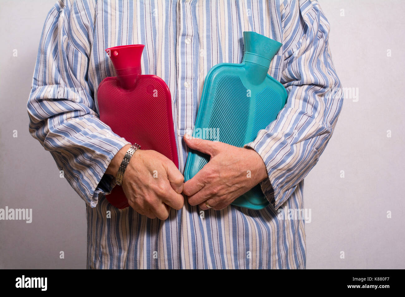 Man in a nightgown holding two hot water bottles - Stock Image