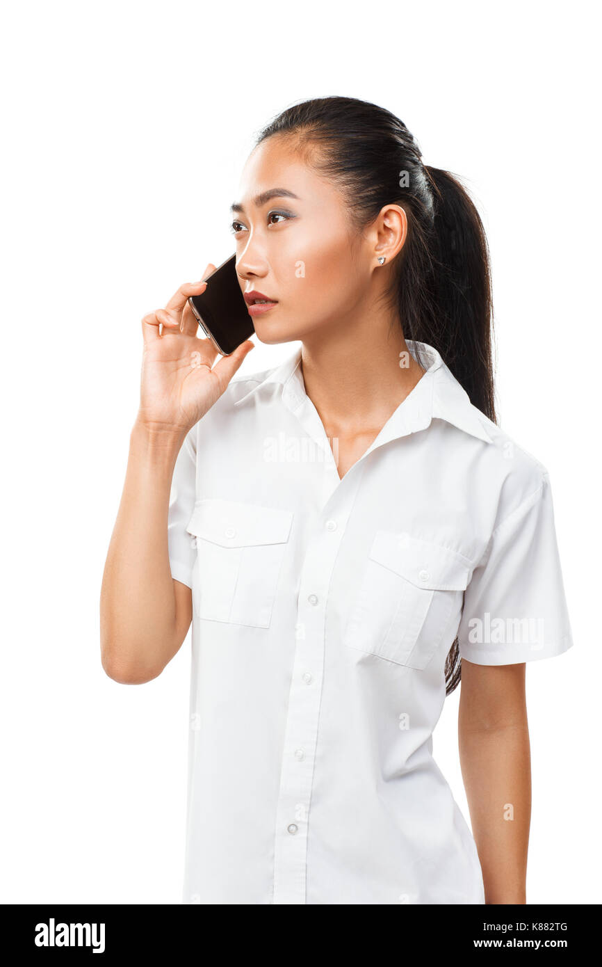 Asian young serious woman in white shirt standing and speaking by mobile phone. Female model has conversation on smartphone. Half body portrait isolat - Stock Image