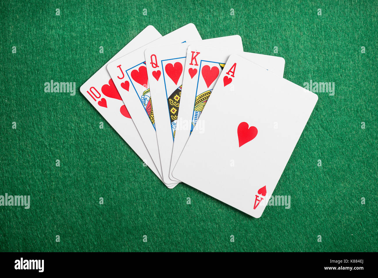 Playing cards flush  on green casino desk  background - Stock Image