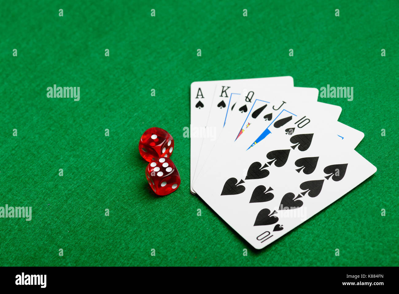 Playing cards flush and red dice on green casino desk  background - Stock Image