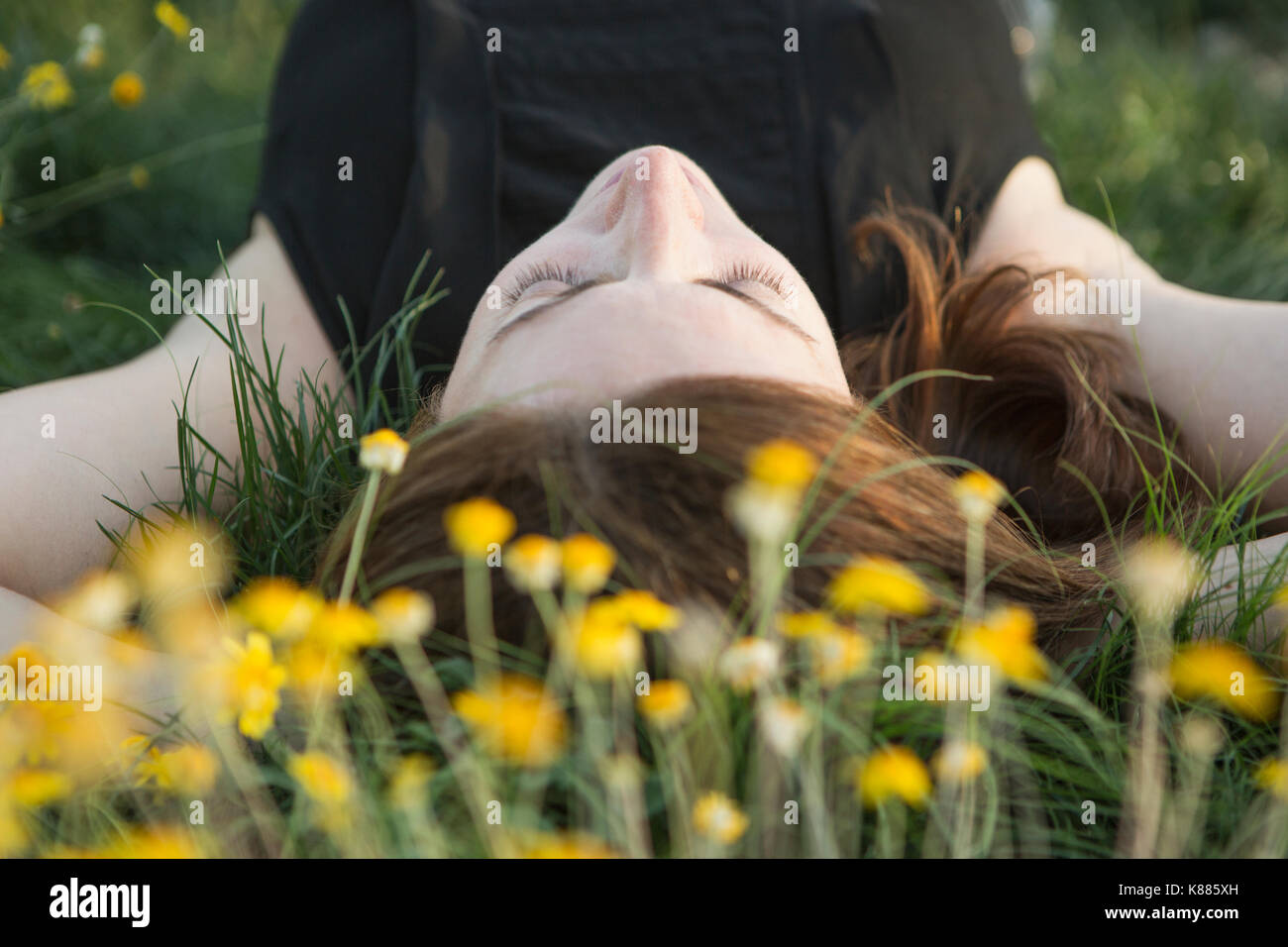 A woman in a black vest top and jeans lying on the grass with her hands behind her head. - Stock Image