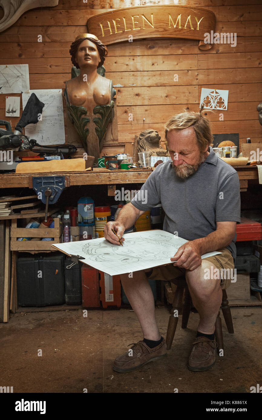 A craftsman, woodworker seated on a stool in a workshop working on a drawing, sketching using charcoal. Surrounded by wooden carved and painted female - Stock Image