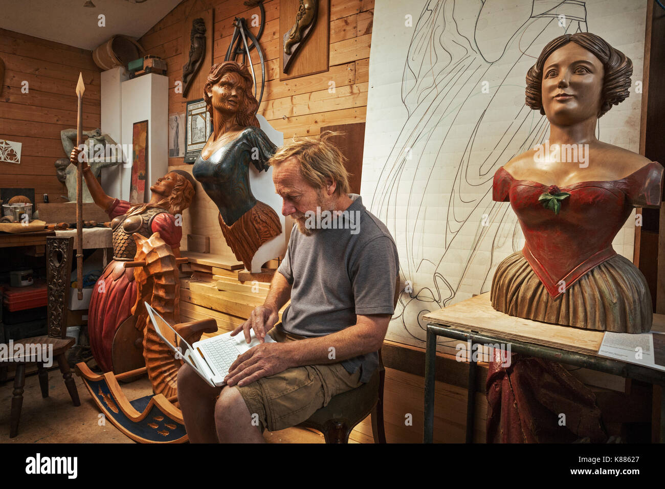 A woodworker, skilled craftsman sitting in a workshop using a laptop on his knees, surrounded by carved wooden female ship's figureheads. - Stock Image