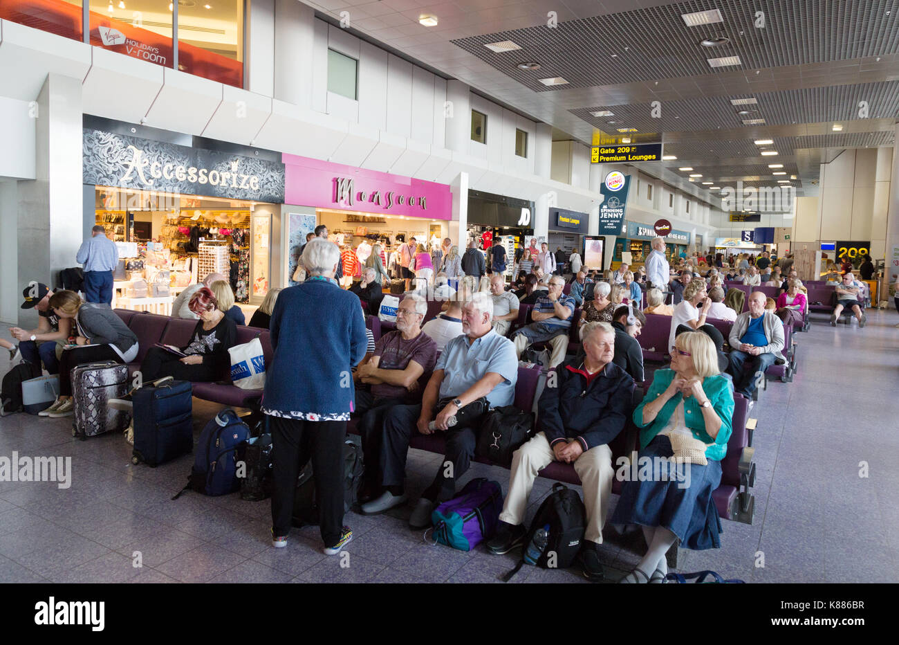 Passengers sitting in departure lounge, Terminal 2, Manchester Airport, England UK - Stock Image