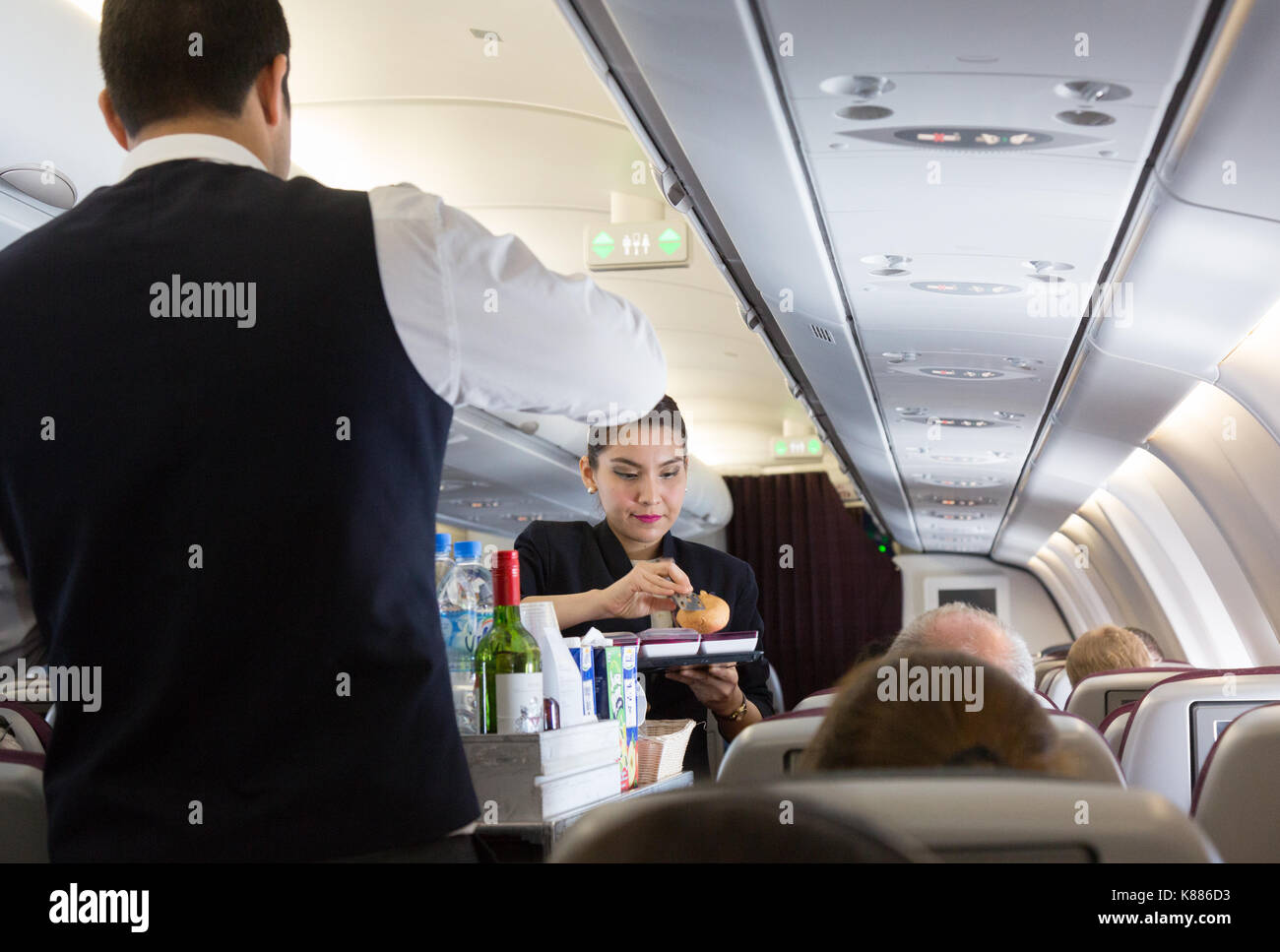 Qatar Airways - cabin crew working on board, - air stewardess serving food on an A330 flight Maldives to Doha - Stock Image