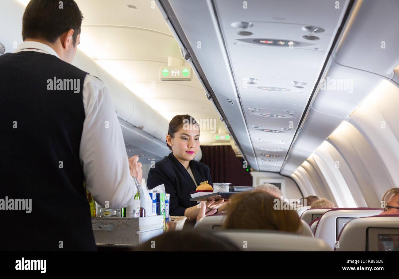 Cabin crew working - Air stewardess serving food, Qatar Airways A330 flight from Maldives to Doha, - Stock Image