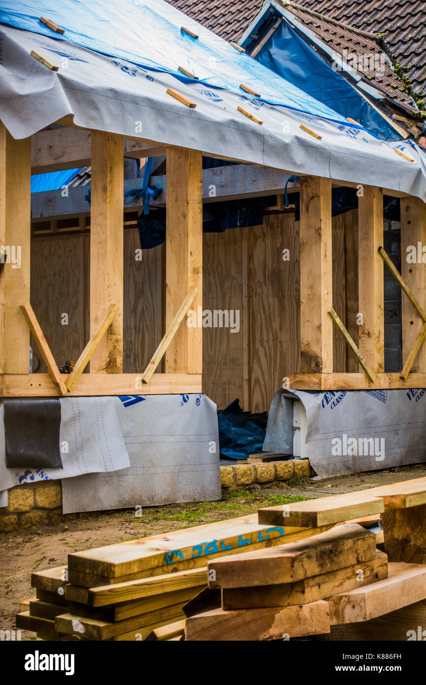 A house extension undergoing construction, with a substantial wooden structure and protective covering over the pitched roof timbers. England, UK. - Stock Image