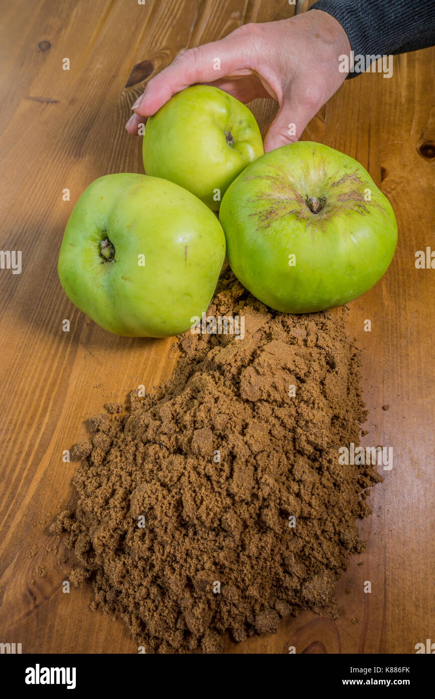 A woman's hand holding one of three raw, Bramley cooking apples, alongside soft brown sugar on a pine kitchen worktop, ready for baking. England, UK. - Stock Image