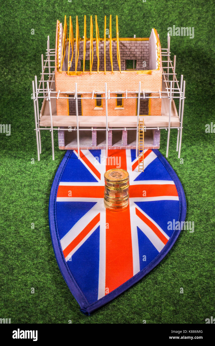Model new build house on a Union Jack, with new sterling pound coins. Concept depicting any cost aspect of the UK property construction industry. - Stock Image