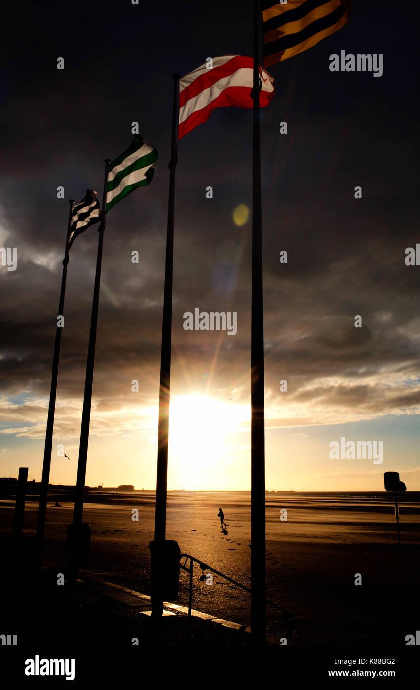 four flags at sunsett on dunkirk beach Stock Photo