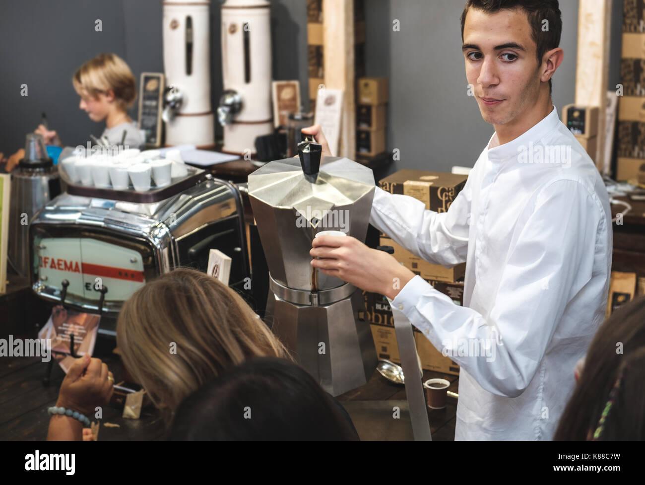 Caffe Italiano at the BAR, italian coffee habits a young italian waiter barista serving coffee from a giant moka coffeepot - Stock Image