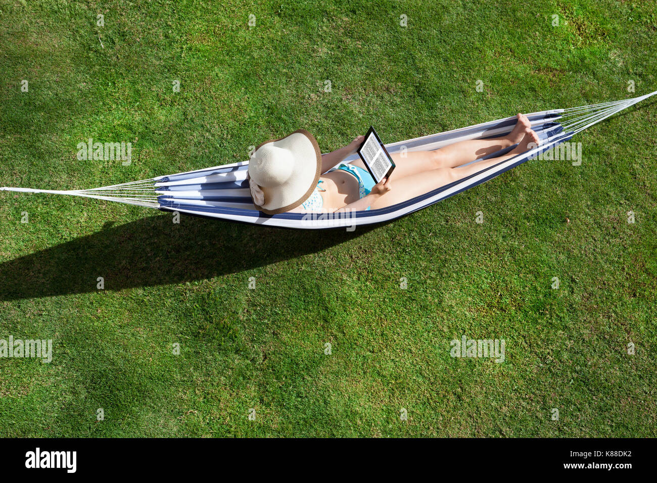 High Angle View Of Young Woman Reading Ebook On Hammock - Stock Image