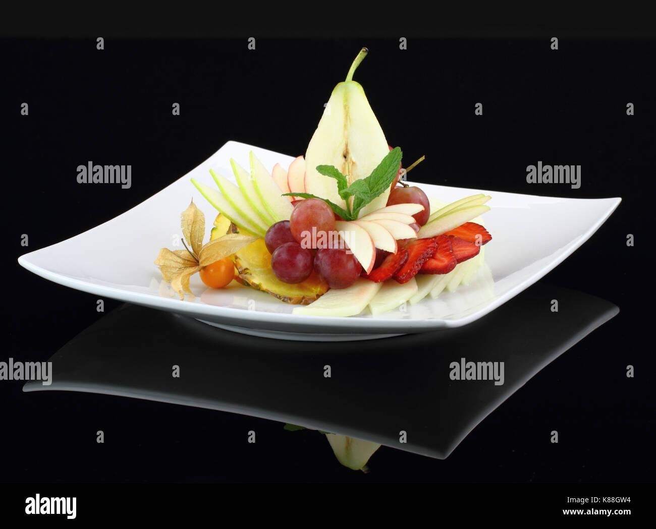 Fruit salad on black background - Stock Image