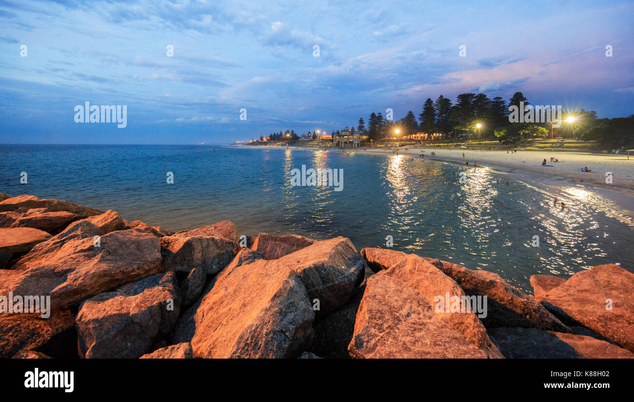 The beach and ocean lit by floodlights on a balmy summer evening. - Stock Image