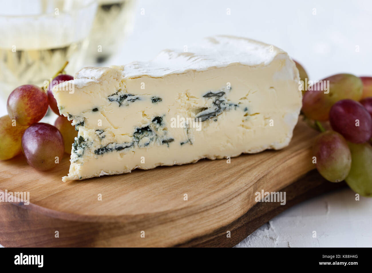 Blue cheese  served with fresh grapes and two glasses of white wine on rustic cutting board, cheese platter - Stock Image
