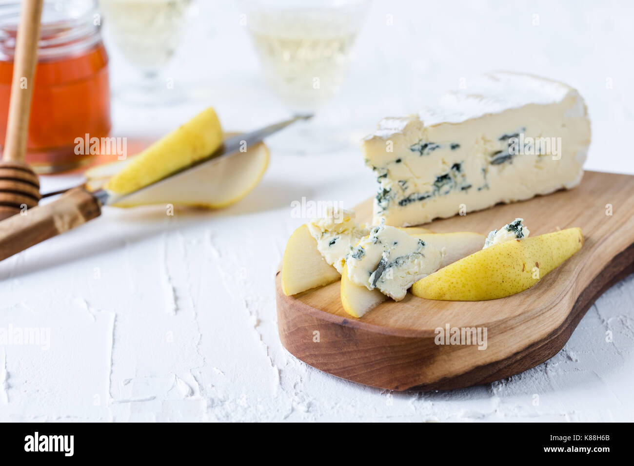 Blue cheese  served with fresh pear and honey on rustic cutting board, cheese platter - Stock Image