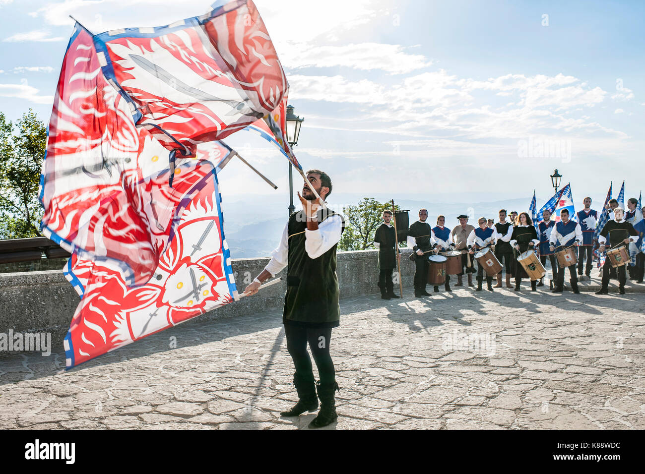 Flag bearer performing a flag juggling demonstration during the annual Medieval Days Festival held in San Marino. - Stock Image