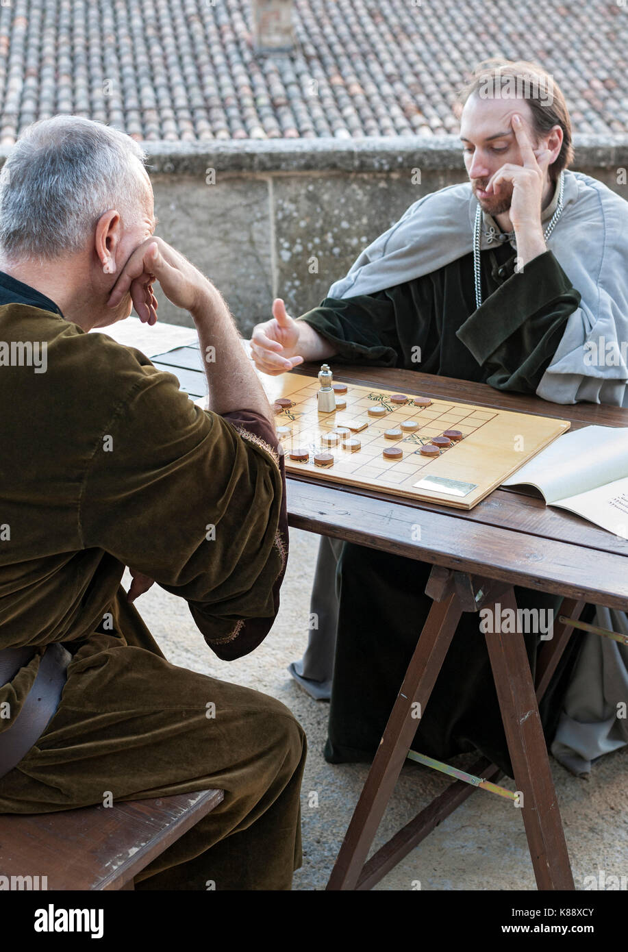 Two men in period costumes playing a board game during the annual Medieval Days Festival held in San Marino. - Stock Image
