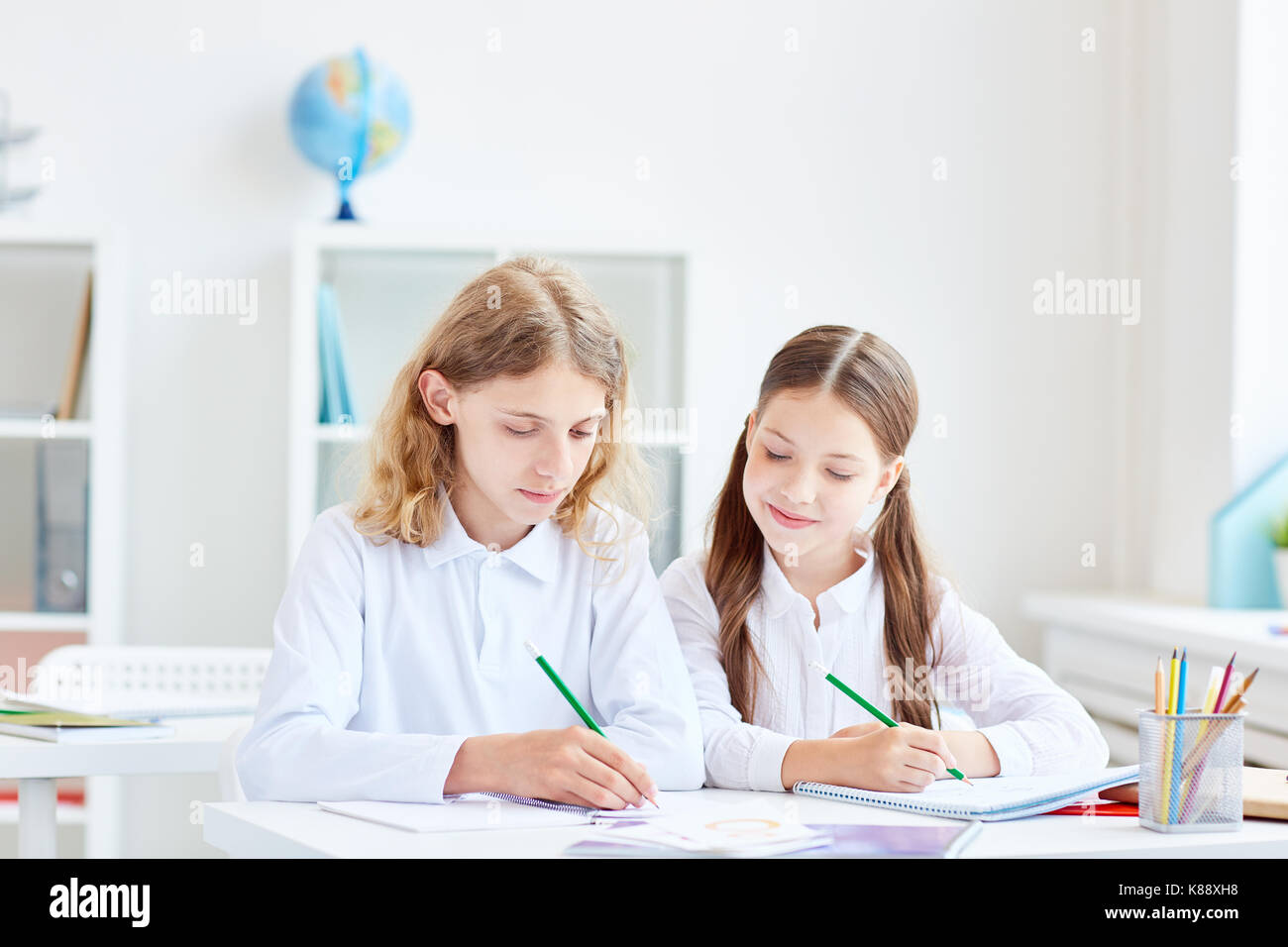 Small group of schoolmates working in team at lesson - Stock Image