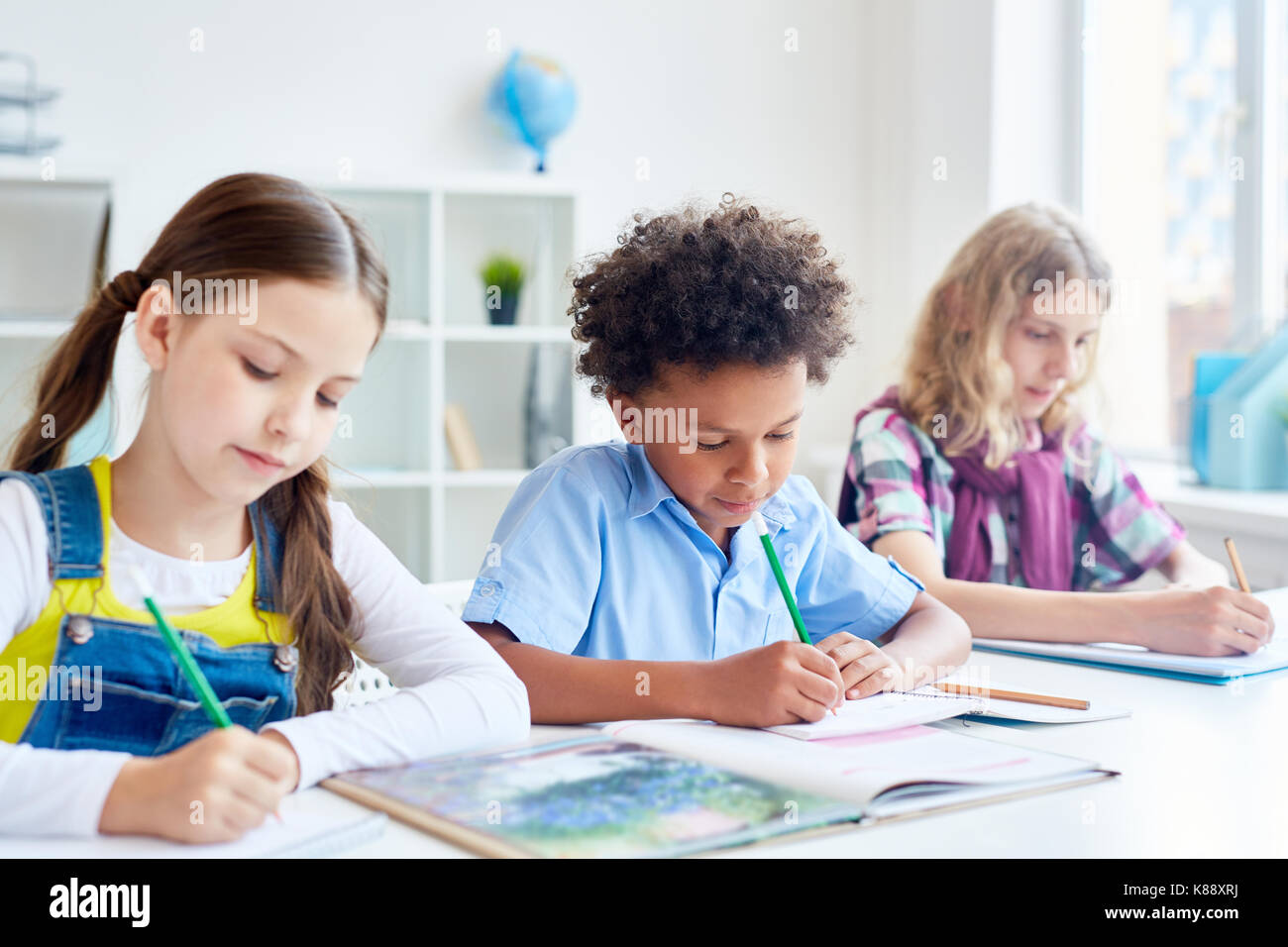Group of schoolmates with pencils drawing at free topic lesson - Stock Image