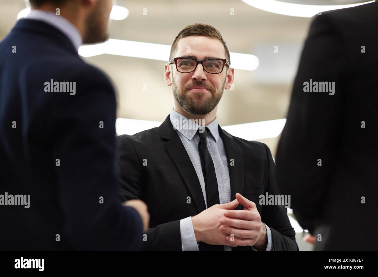 Confident financier in formalwear listening to one of colleagues at meeting - Stock Image