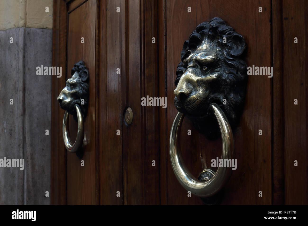 Lion's head door knockers, wooden door in marble frame. Shallow focus. Rome, Italy. - Stock Image