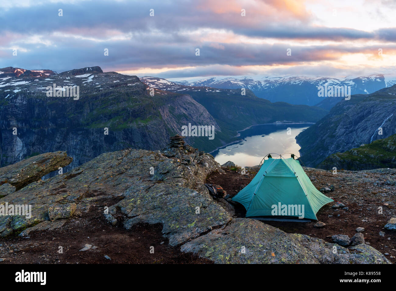 Alone tent near Trolltunga rock - most spectacular and famous scenic cliff in Norway - Stock Image