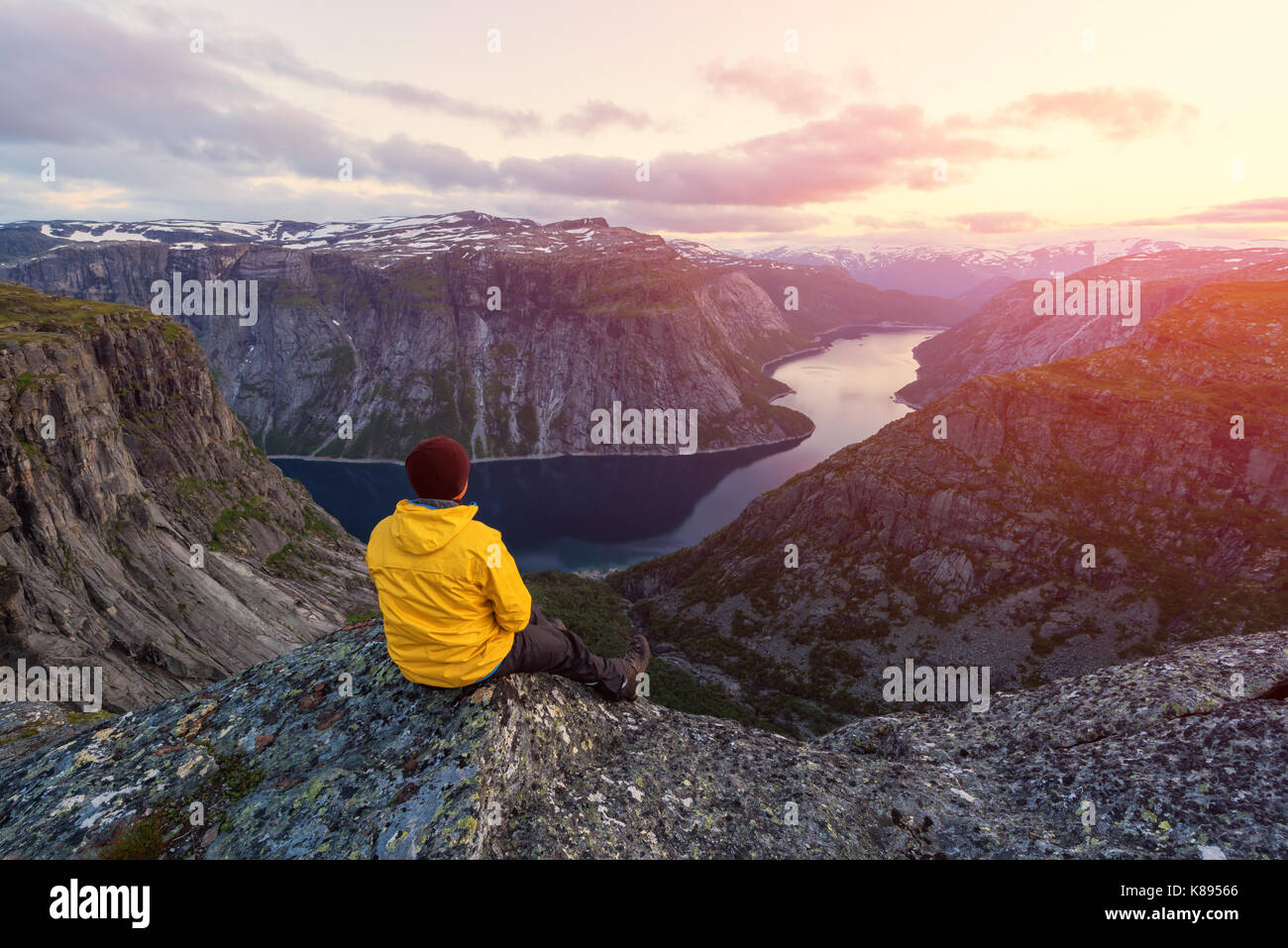 Alone tourist on Trolltunga rock - most spectacular and famous scenic cliff in Norway - Stock Image