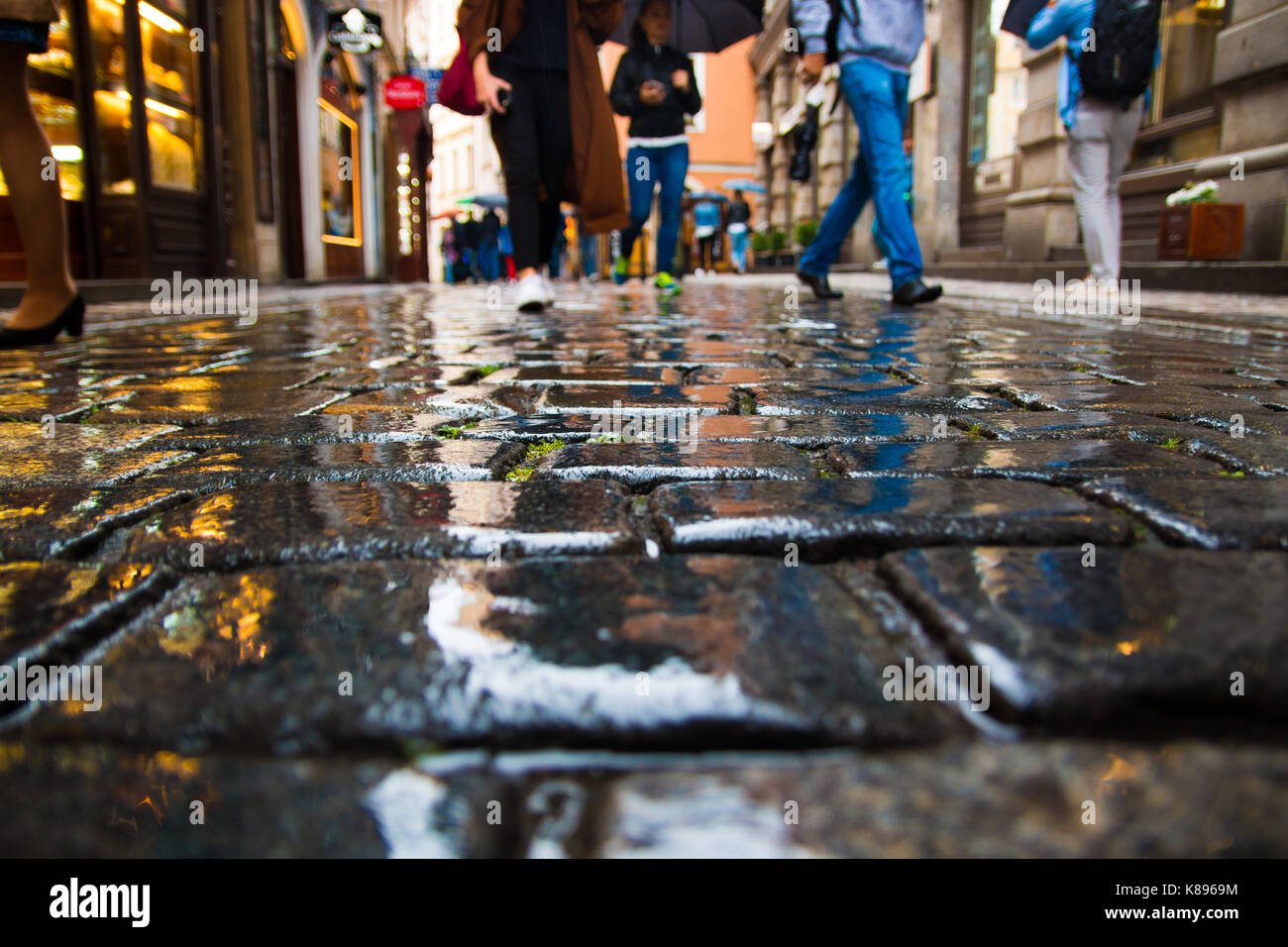 People walking on wet paving stones in rainy day in old town of Prague Stock Photo