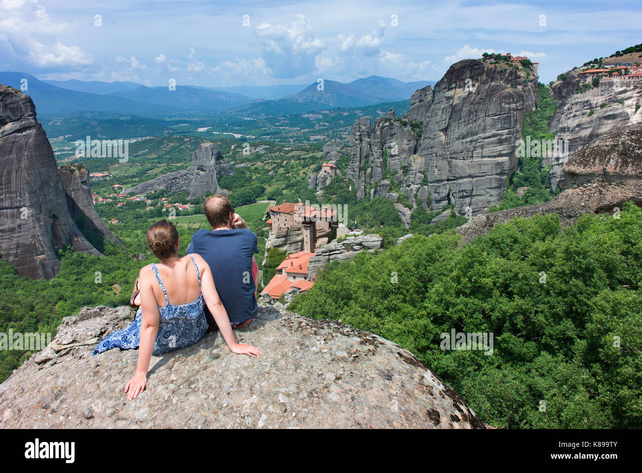 A young couple admire the view of some of the monasteries at Meteora. - Stock Image