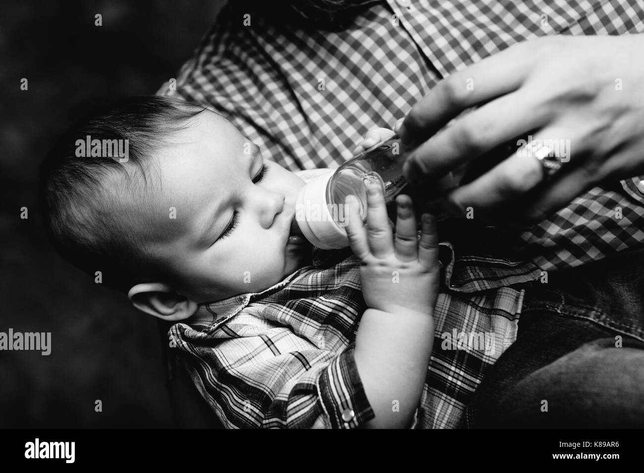 father's hand holding baby boy eating from the bottle - Stock Image