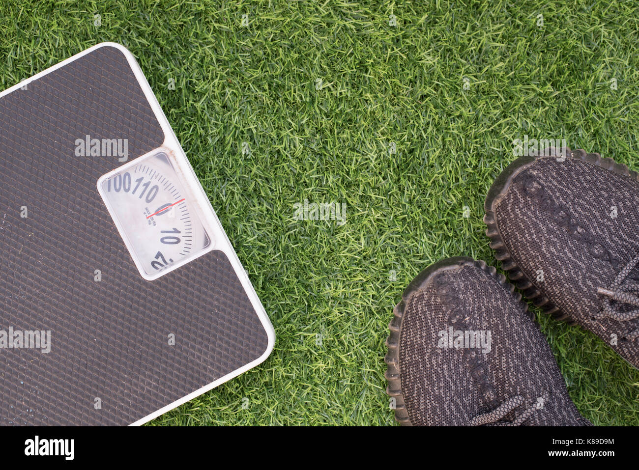 Fitness and weight loss concept, white scale and sport shoe on a grass, top view, free copy space - Stock Image
