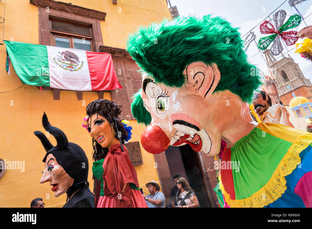 Giant papier mâché puppets called mojigangas dance in the streets during a children's parade celebrating - Stock Image