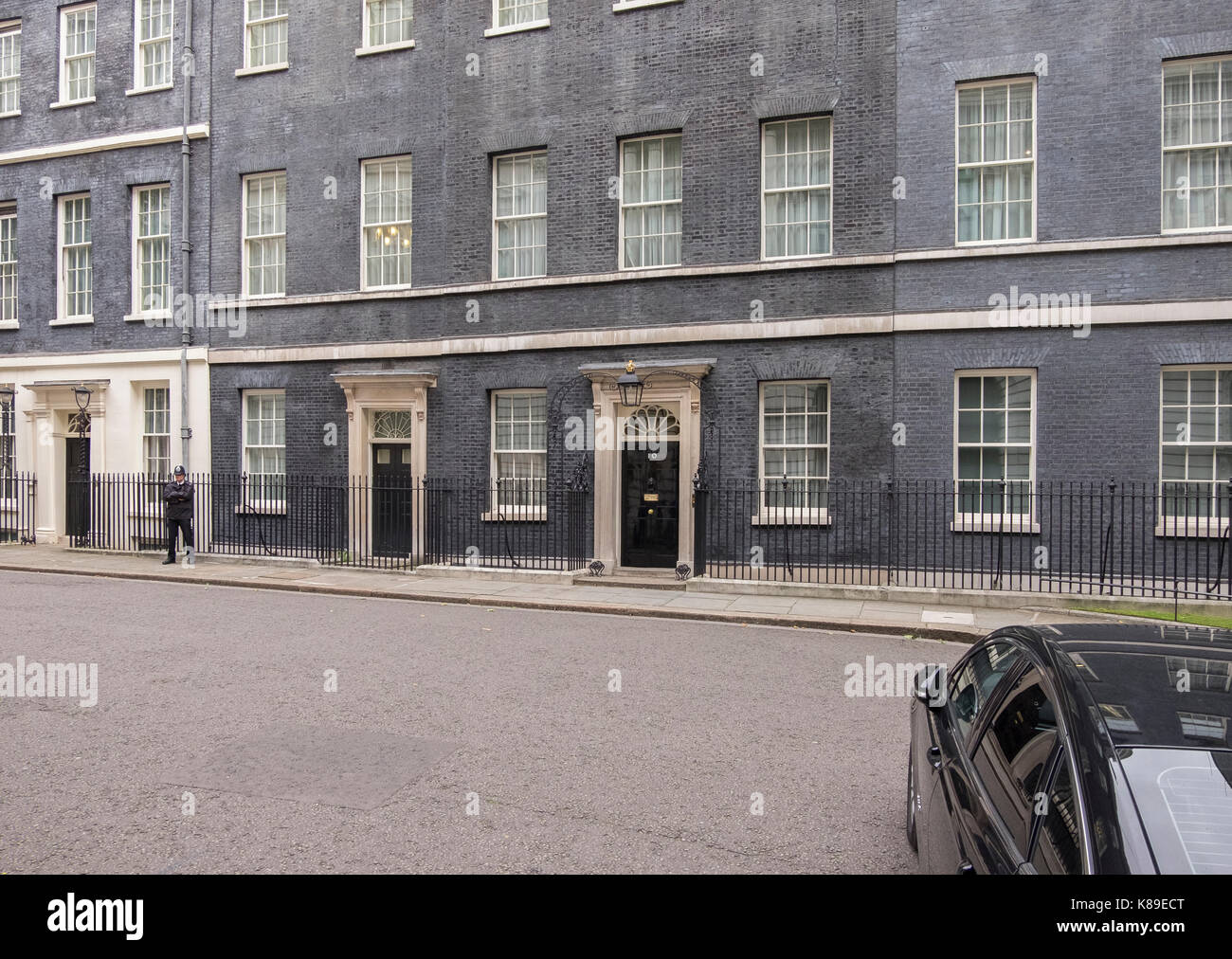 Metropolitan police officer and ministerial car outside No 10 Downing Street, London, UK. Credit: Malcolm Park/Alamy - Stock Image