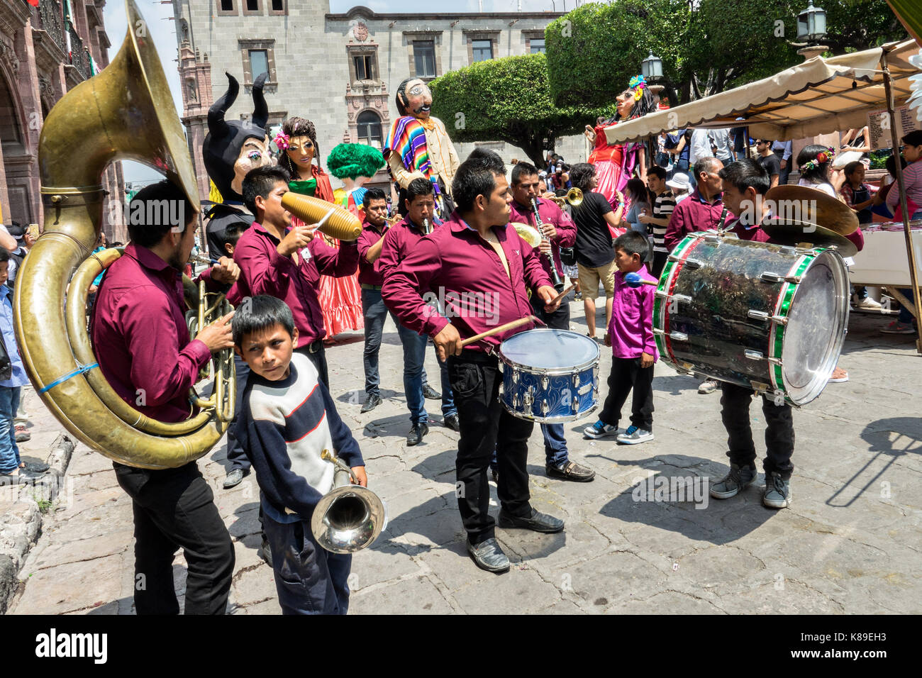 A brass band leads a procession of giant papier mache puppets called mojigangas during a children's parade celebrating - Stock Image