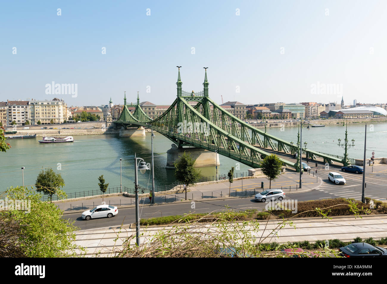The Liberty Bridge in Budapest, Hungary with some old trams in the foreground passing by. Stock Photo