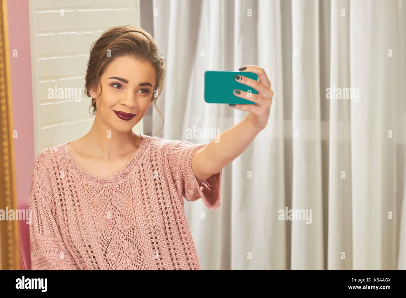Woman smiling and taking selfie. - Stock Image
