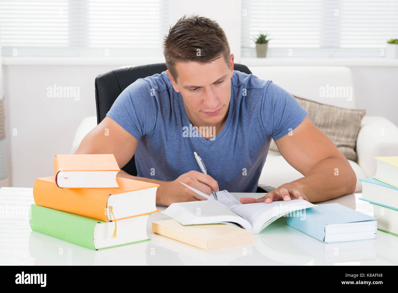 Young Man Reading Books At Desk In Living Room - Stock Image