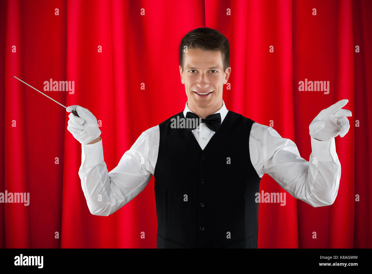 Male Orchestra Conductor Holding Baton Over Red Curtain - Stock Image