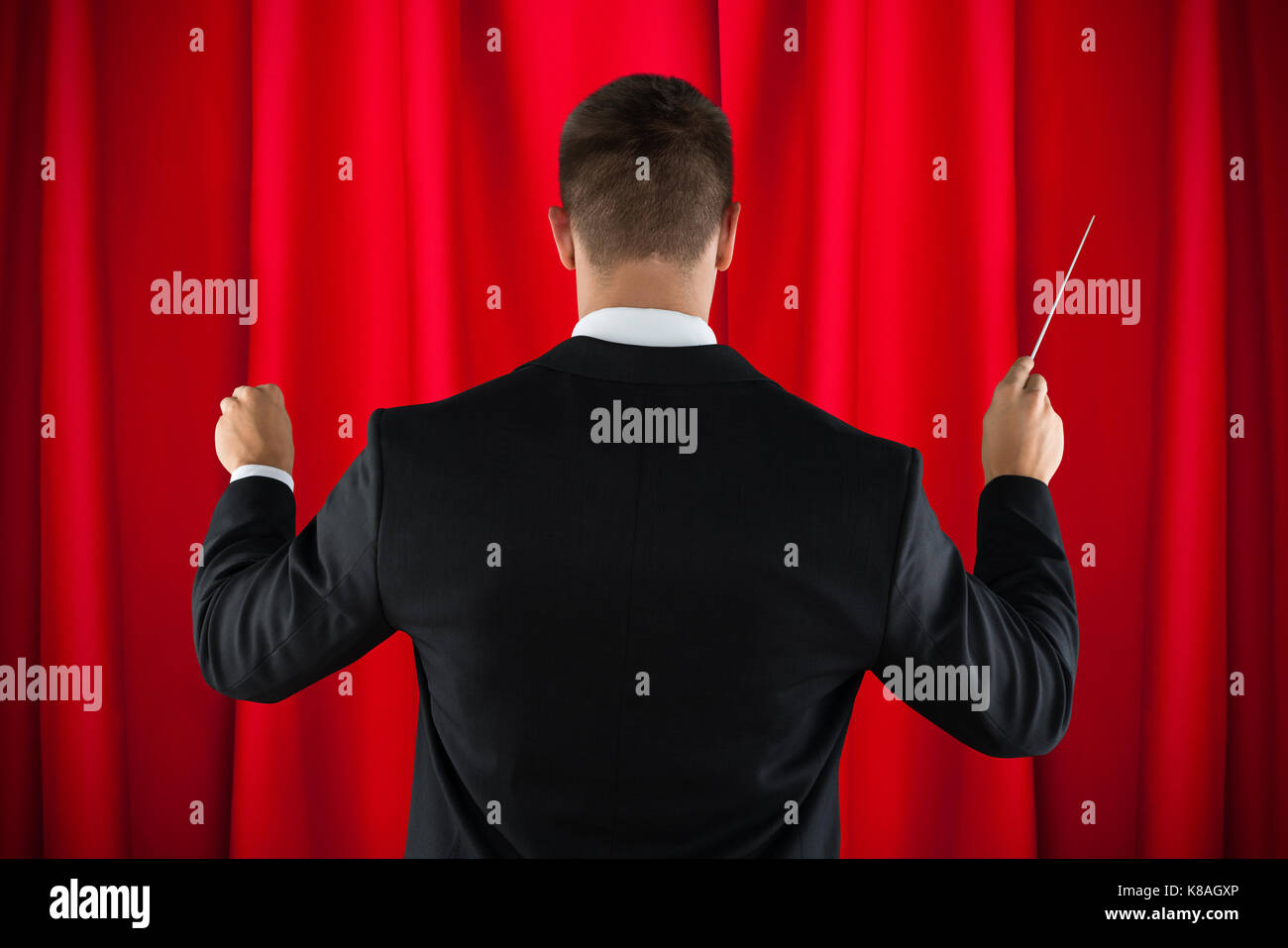 Rear View Of Male Orchestra Conductor Directing With His Baton - Stock Image
