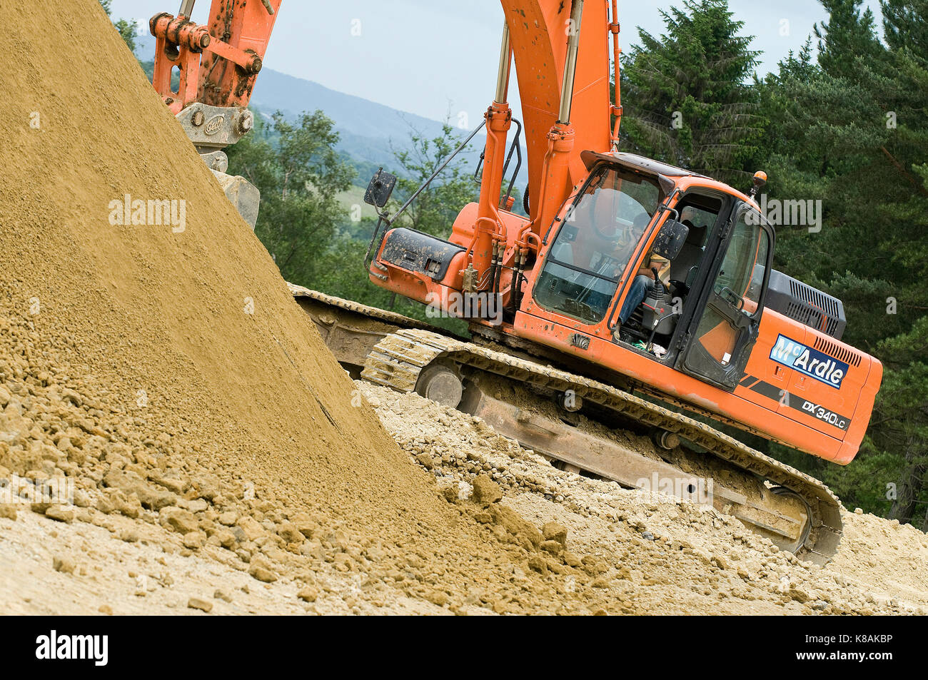 a digger or JCB large plant or machinery working on a building site moving a pile of spoil or sand with a scoop - Stock Image
