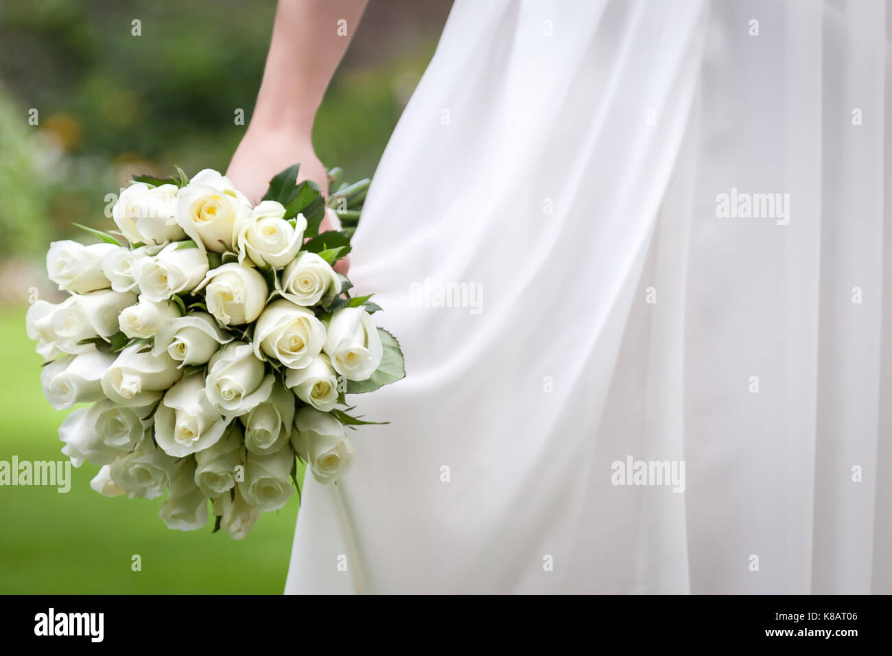 A wedding bride's bouquet of white/yellow rose flowers with wedding dress. - Stock Image