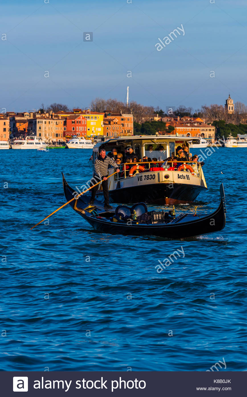 A gondola and vaporetto (water bus) in the Venice Lagoon, Venice, Italy. - Stock Image