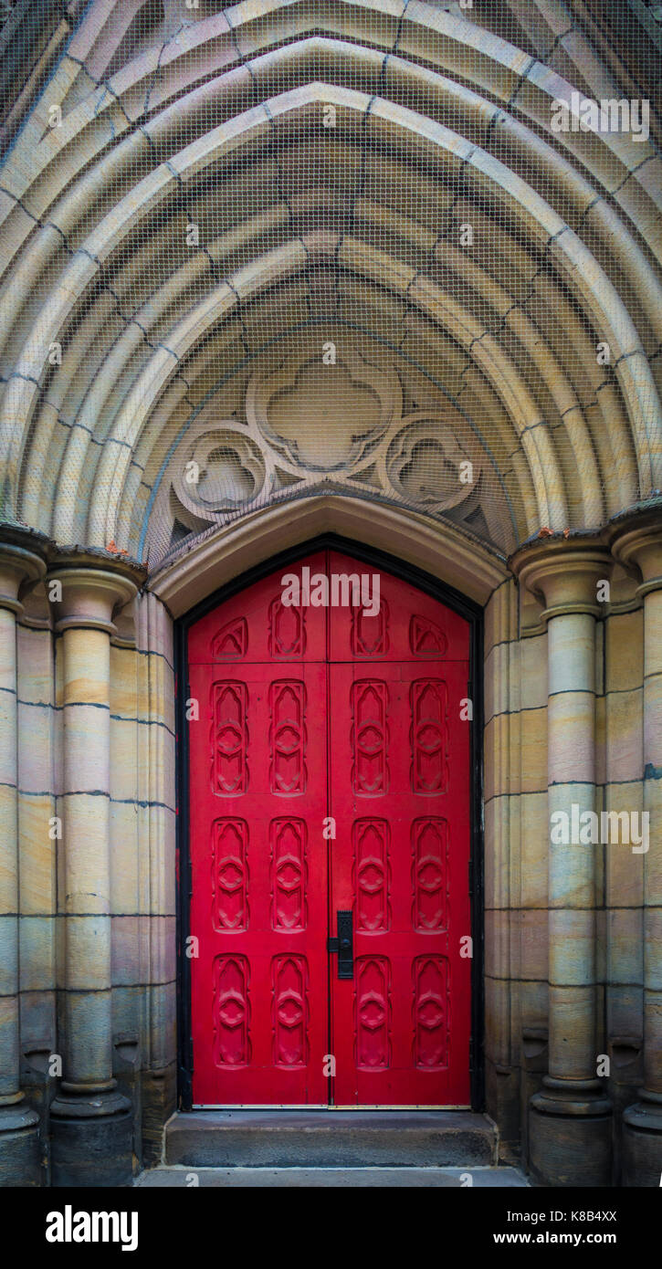 An ornate red door on the front of the Trinity Episcopal Cathedral, downtown Pittsburgh, Pennsylvania, USA - Stock Image