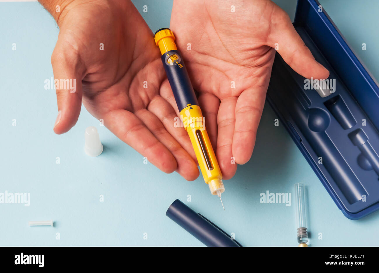 A man holds a syringe for subcutaneous injection of hormonal drugs in the IVF protocol (in vitro fertilization). - Stock Image