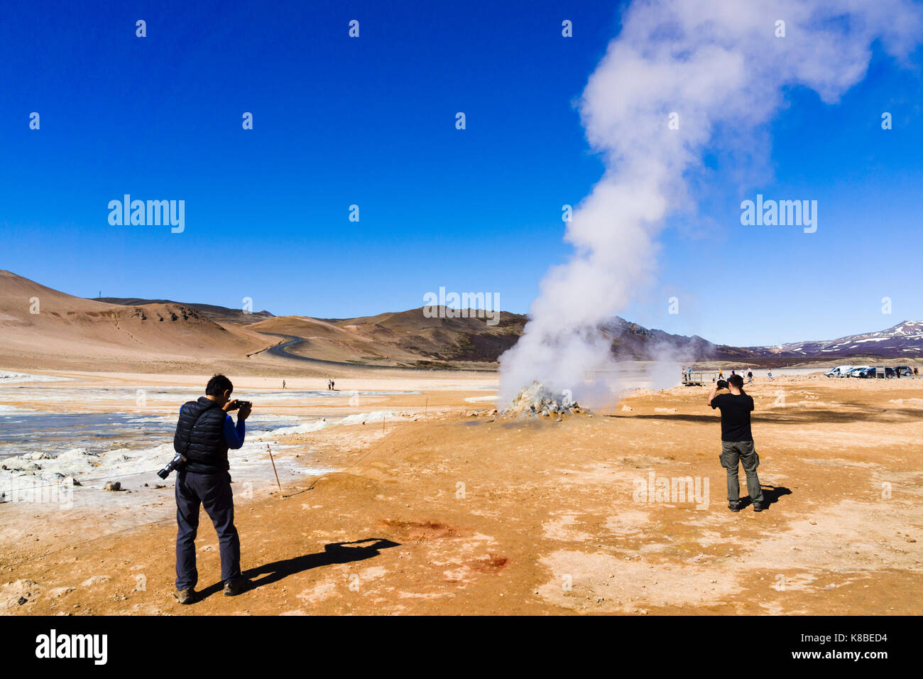 Tourists photographing a steaming fumarole at Námafjall Hverir geothermal area, Iceland - Stock Image