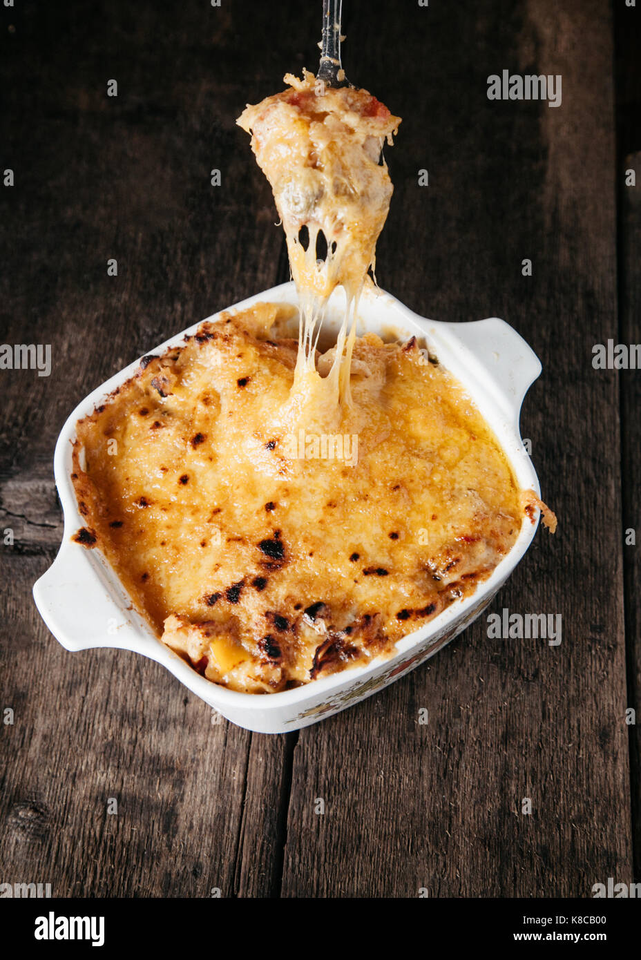 Creamy baked chicken casserole layered with shreded cheddar cheese on wooden surface - Stock Image