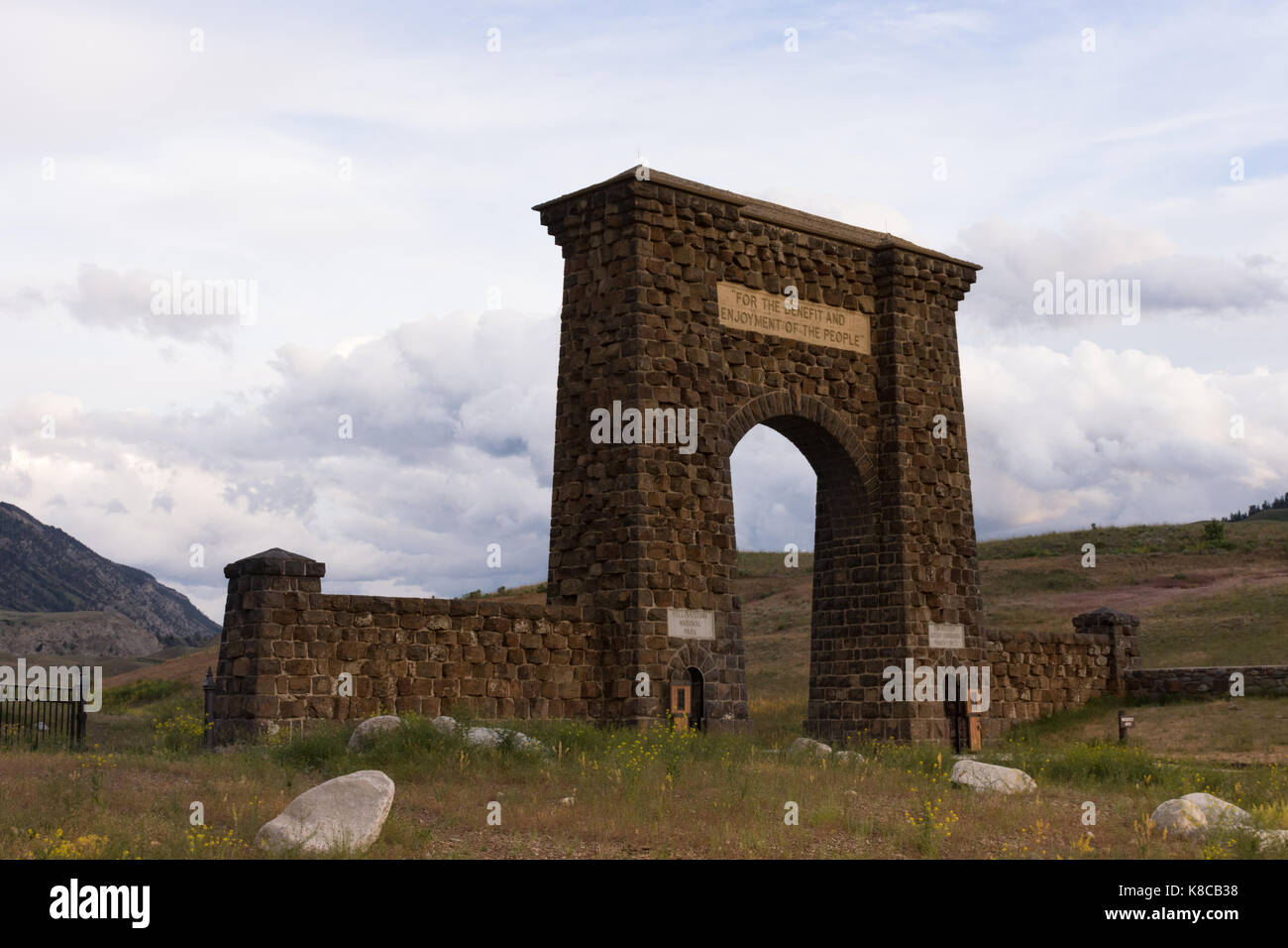 The Roosevelt Arch at the entranace of Yellowstone National Park with mountains and foothills in the background - Stock Image