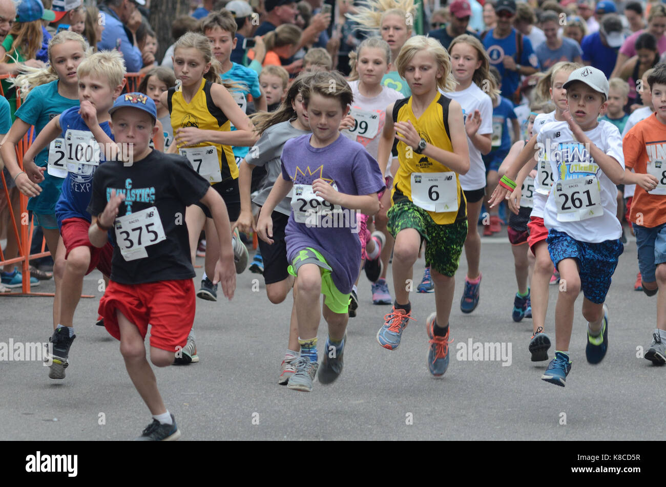Young racers take flight at the start of the Kids Race during the Pearl Street Mile. The children and adolescents - Stock Image